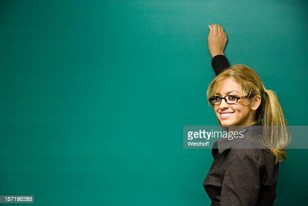 A teacher smiling and writing on a blank chalkboard