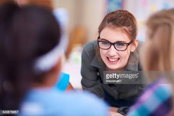 Teacher smiling at schoolgirls in classroom