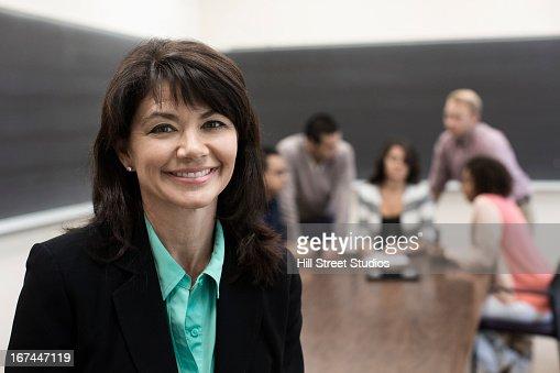 Teacher smiling in classroom : Stock Photo