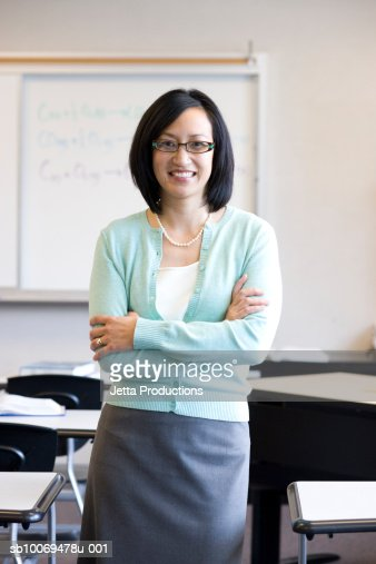 Teacher smiling in classroom, portrait