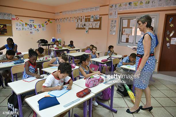 A teacher speaks to students in a classroom at the JeanMermoz international French school following its reopening in Abidjan on June 2 2015 The...