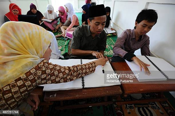 A teacher speaks to visually impaired students as they read the Braille Quran at The Foundation for The Education of Blind Children on July 17 2014...