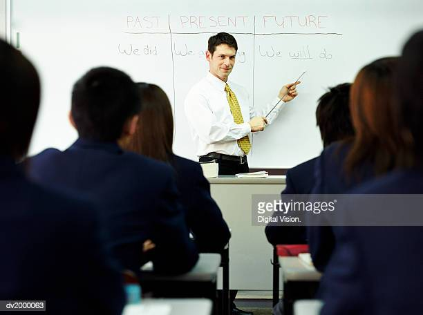 Teacher Standing at the Head of a Class Pointing to Words on a White Board