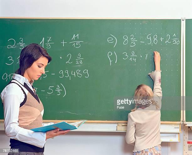 Teacher Standing Beside Girl at Blackboard in Classroom
