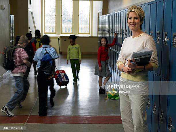 Teacher standing in busy school hallway, portrait