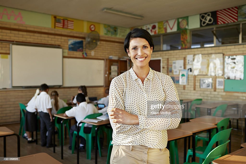 Teacher standing in classroom and smiling