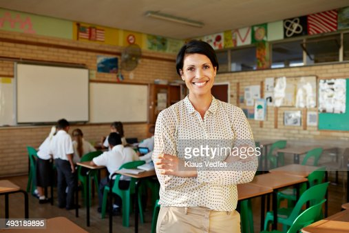 Teacher standing in classroom and smiling : Stock Photo