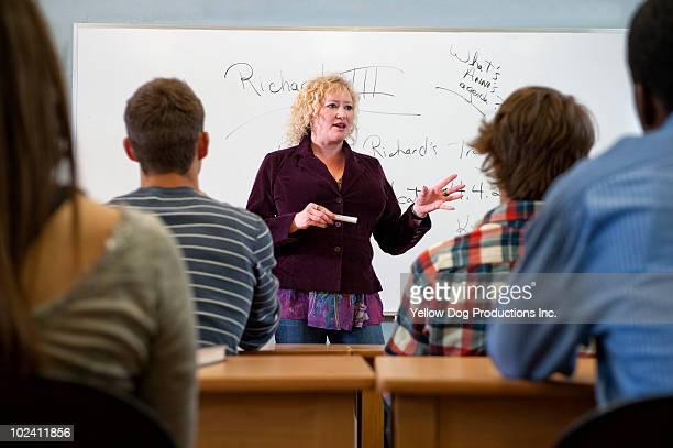 Teacher standing in front of class teaching