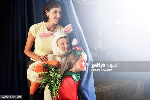 Teacher standing with children (5-7) in costumes behind stage curtain