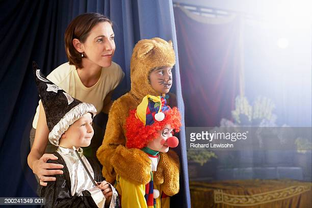 Teacher standing with children (4-8) in costumes behind stage curtain