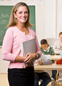 Teacher standing with notebook in classroom and smiling at camera. Students working in background. Vertical shot.