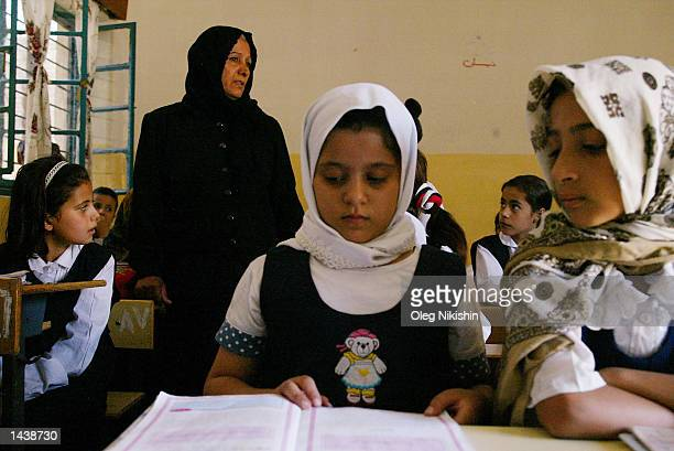A teacher stands in the classroom as students do classwork at the girls' primary school in the Alalawi district September 29 2002 in Baghdad Iraq UN...
