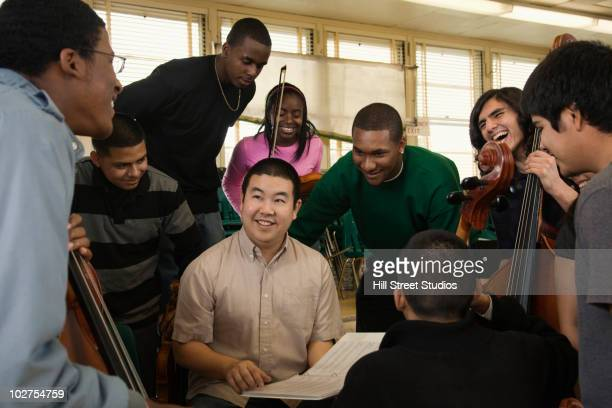 Teacher talking to high school orchestra students