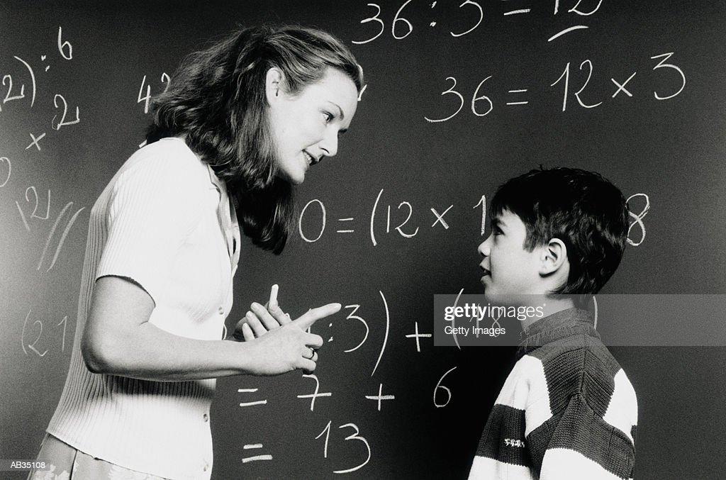 Teacher talking to student (6-8) by chalkboard (B&W) : Stock Photo