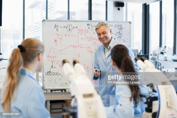 Teacher talking to students in lab