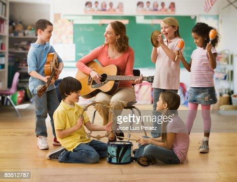 Teacher teaching music lesson to children : Foto de stock