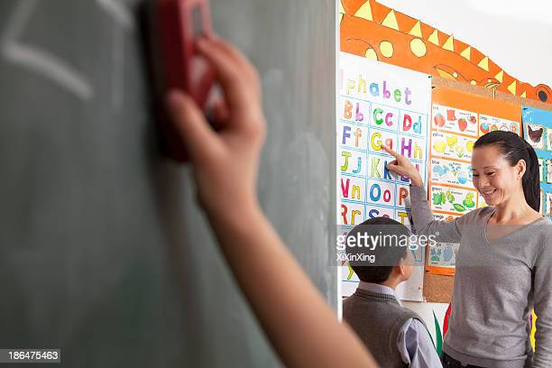 Teacher teaching student the alphabet