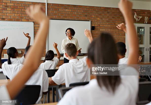 Teacher teaching students with raised hands