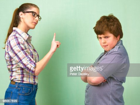 Teacher telling off overweight school boy : Stock Photo