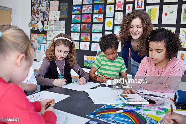 Teacher together with children drawing