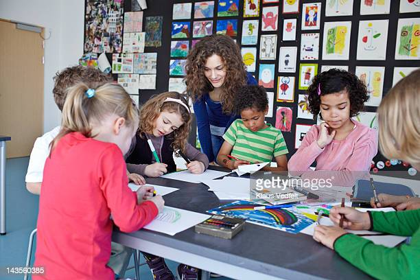 Teacher together with kids drawing in classroom
