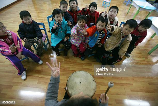 A teacher trains hearingimpaired children with a drum at the Hearing and Language Rehabilitation Center for the Deaf Children of Chongqing Disabled...