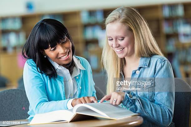 Teacher tutors high school student in library