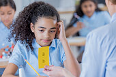 African American student has a concerned expression on her face while her teacher shows her a flash card.