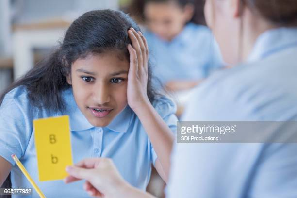 Teacher uses flashcards with female student