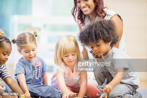 Teacher Watching Children Play with Toys
