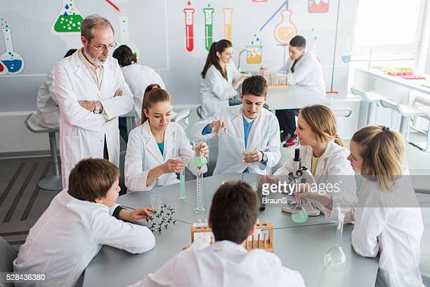 Teacher watching over students on a chemistry class in laboratory.