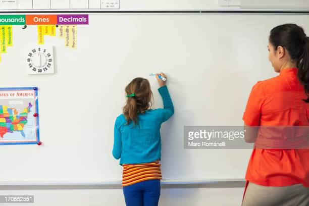 Teacher watching student write on whiteboard in classroom