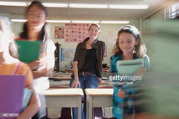 Teacher watching students leave classroom
