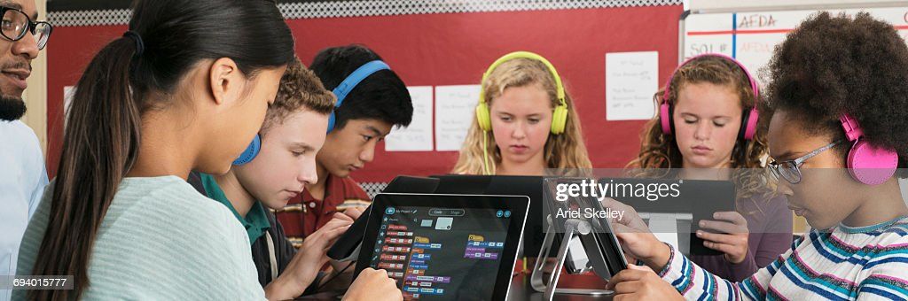Teacher watching students using digital tablets in classroom : ストックフォト