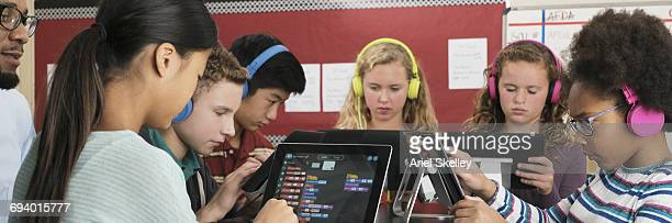 Teacher watching students using digital tablets in classroom