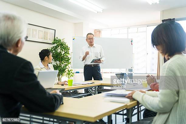Teacher with adult students in community college