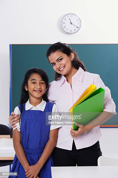 teacher with arm around student, both smile at camera
