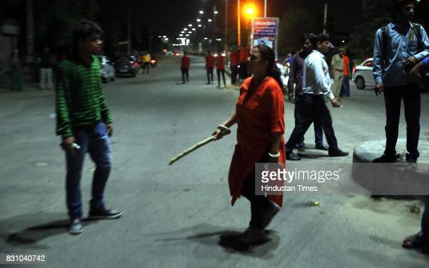 A teacher with baton manages the passerbys and onlookers during the 'Meri Raat Meri Sadak' campaign in which thousands of girls and boys from...