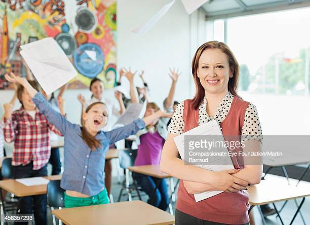 Teacher with celebrating students in classroom