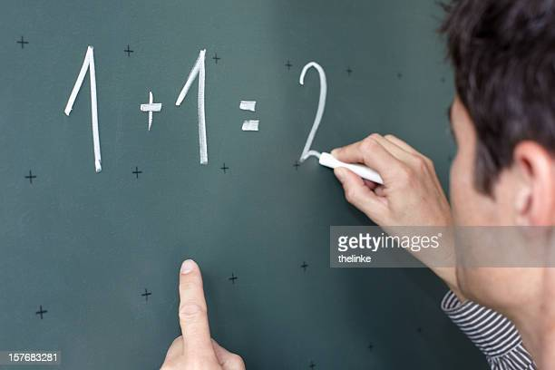 Teacher with chalk calculating on a black board