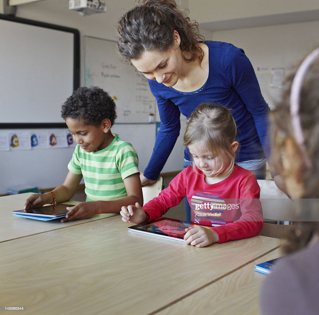 Teacher with children using tablets : Stock Photo
