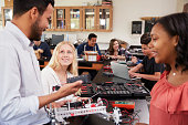 Teacher With Female Pupils Building Robotic Vehicle In Science Lesson