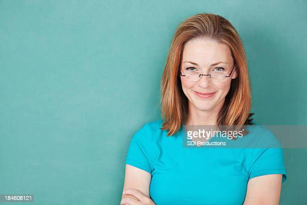 teacher with glasses smiling in front of green chalkboard