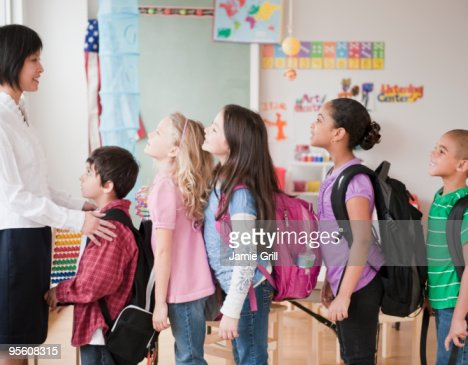 Teacher with group of students standing in line : Stock Photo