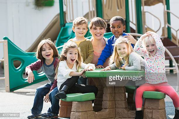 Teacher with preschoolers on playground laughing