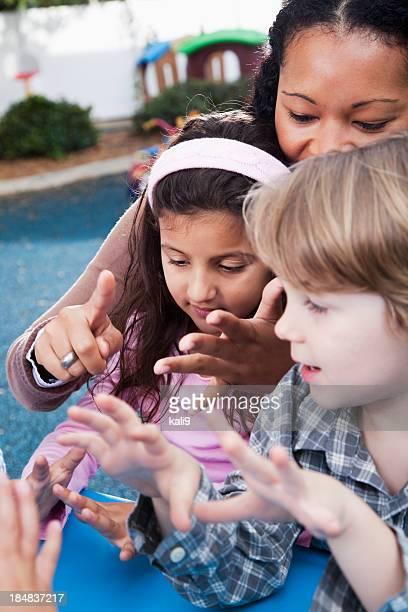 Insegnante con bambini in età prescolastica sul parco