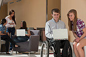 Teacher with spinal cord injury and students working on a laptop