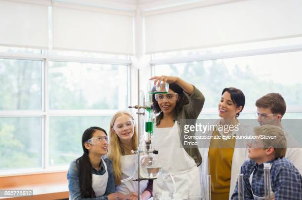 Teacher with students conducting scientific experiment