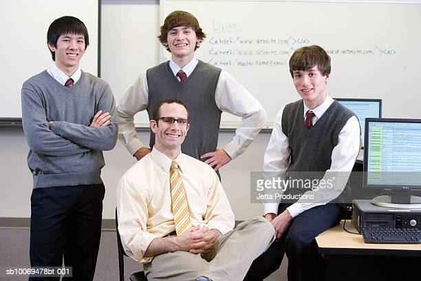 Teacher with three school boys (16-18) in computer room, portrait