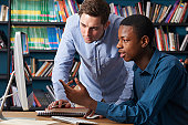 Teacher Working With Male Teenage Pupil At Computer